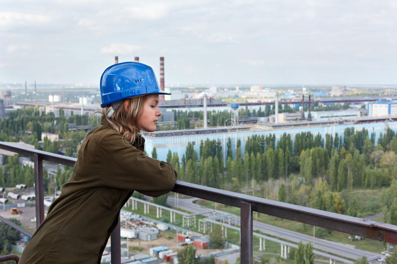 Worker female in the factory. Standing in helmet on the altitude and looking down. Plant area on background stock photography