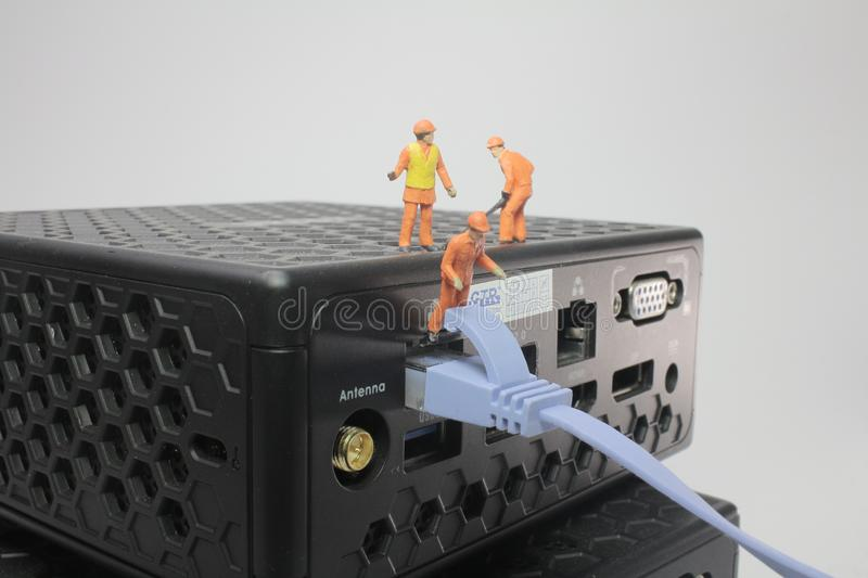 A worker figurines posed working on network. Worker figurines posed as if working on a network stock image