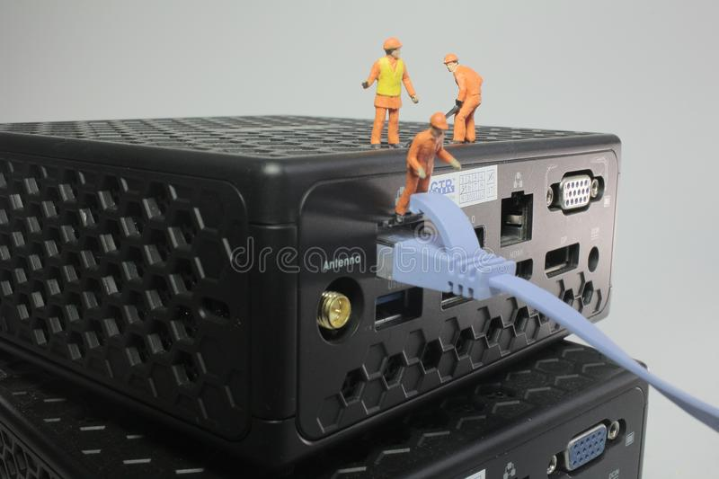 A worker figurines posed working on network. Worker figurines posed as if working on a network stock photo
