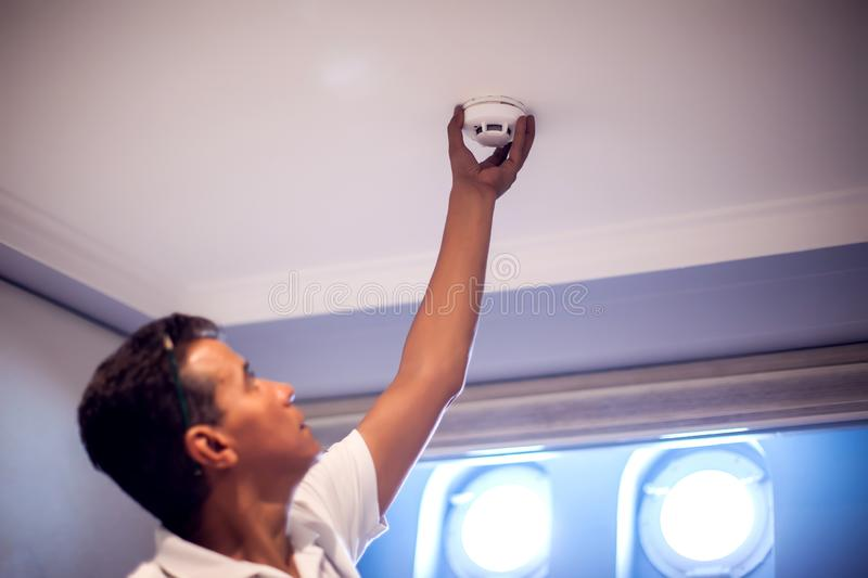 A man worker fix fire system on the ceiling. Building, renovation and electricity concept royalty free stock photography