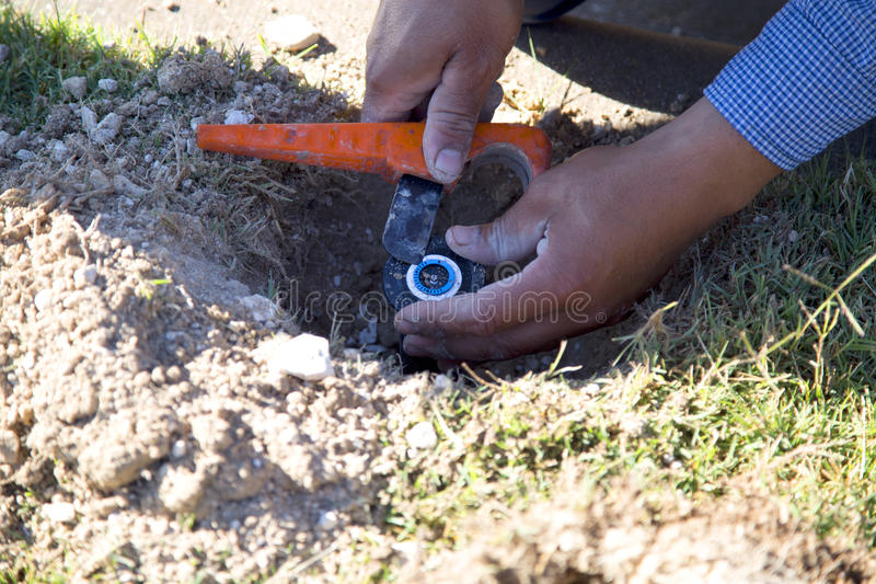 Worker fix lawn sprinkler. A worker is fixing lawn sprinkler stock image