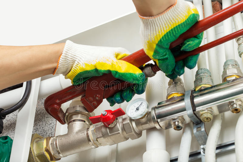 Worker fixing heating system. Worker hands fixing heating system stock images