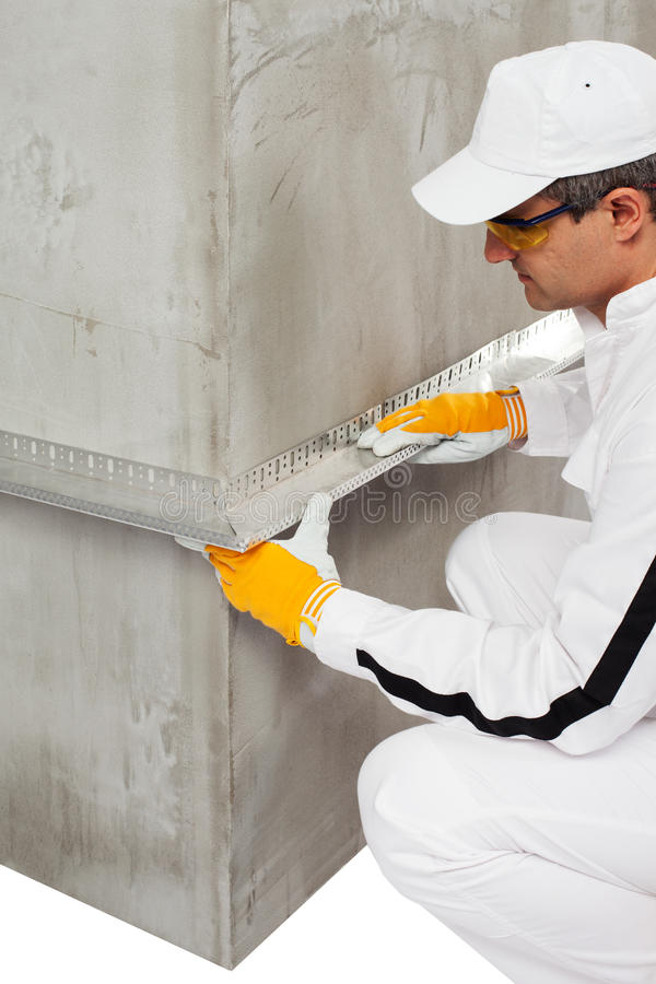Worker fixing a lath on a corner. Worker fixing a lath on a cement corner royalty free stock images