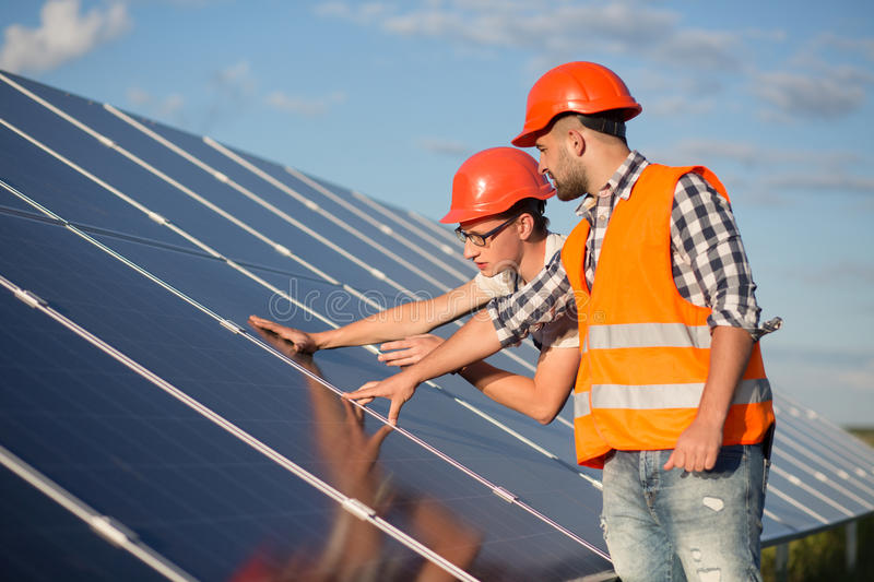 Worker and foreman maintaining solar energy panel. Technicians checking equipment for solar energy station stock photography
