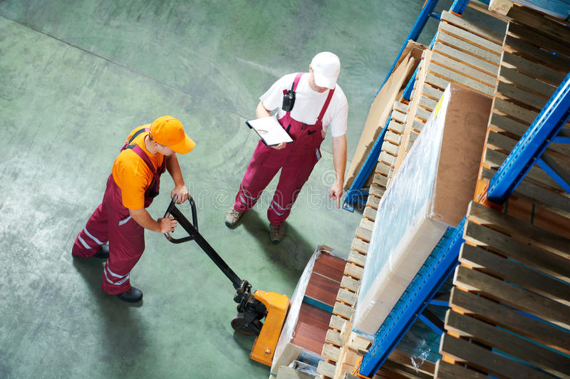 Worker with fork pallet truck royalty free stock images
