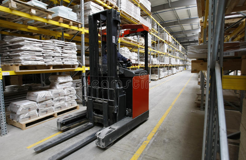 Worker with forklift in wood warehouse royalty free stock image