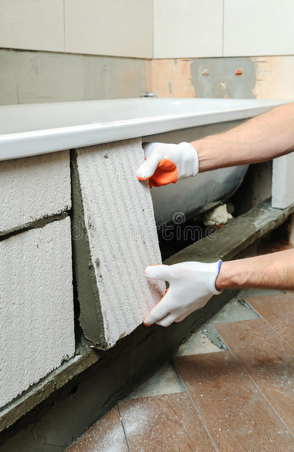 Worker forms the sidebar bath. Worker places aerocrete blocks and forms the sidebar bath stock photos