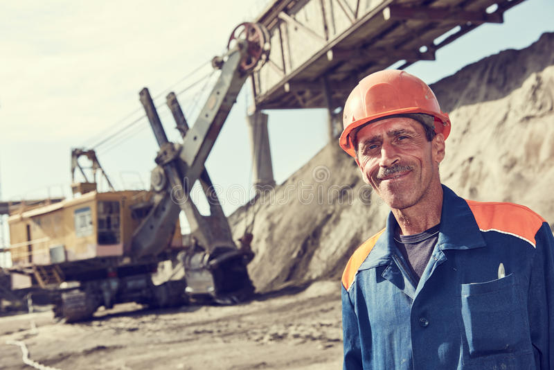 Worker in front of heavy excavator loading gravel into train stock photo