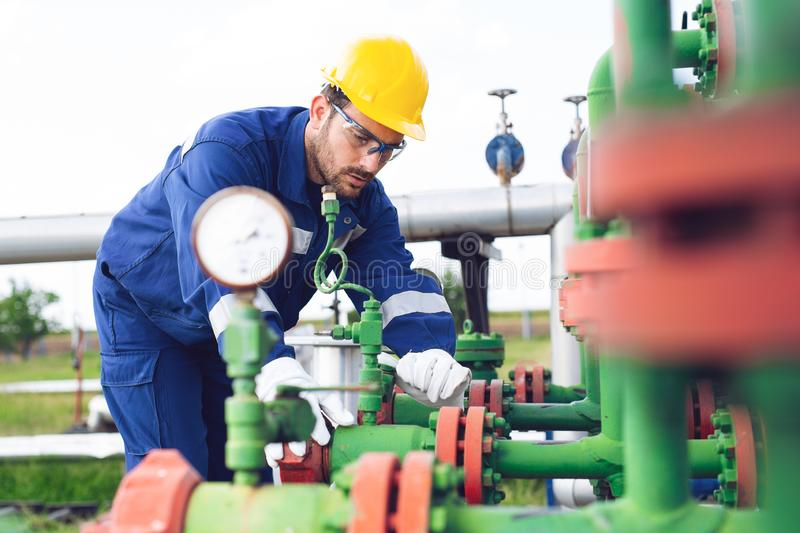 The worker of the gas refinery. Young worker of the gas refinery royalty free stock images