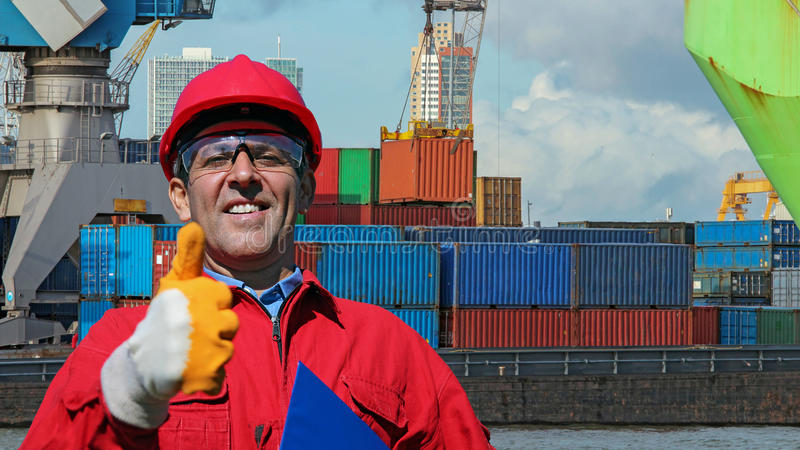 Worker Gesturing Thumb Up Near Container Terminal stock photo