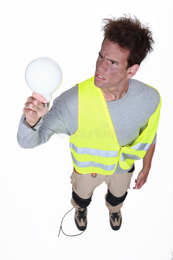 Worker getting an electric shock. From a light bulb royalty free stock photo