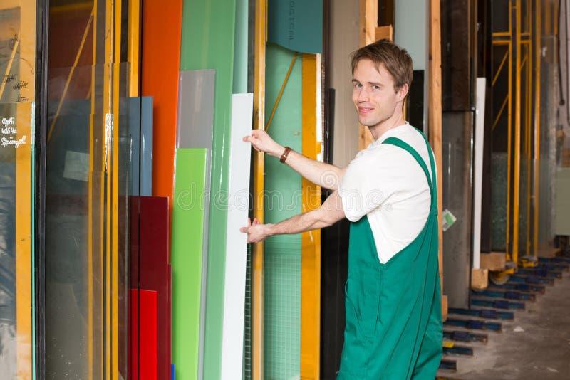 Worker in glass glazier's workshop. Glazier working in glass warehouse stock photos