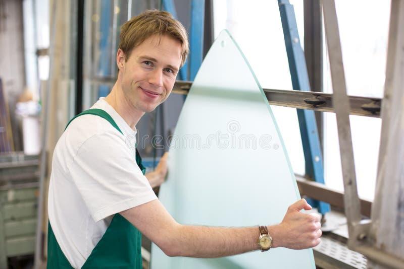 Worker in glazier's workshop handling glass. Glazier handling a piece of glass in workshop stock photography