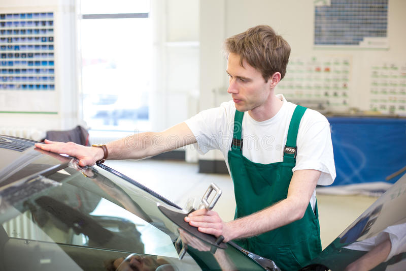 Worker in glazier's workshop installs windshield. Glazier installs windscreen into car in garage royalty free stock image