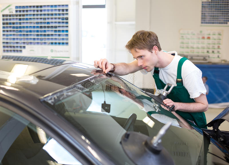 Worker in glazier's workshop installs windshield. Glazier installs windscreen into car in garage royalty free stock images