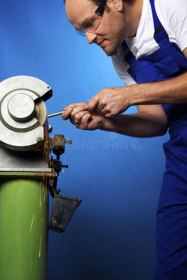 Worker on grinding bench stock photography