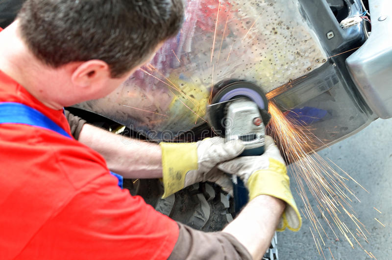 Worker grinding car panel stock photography