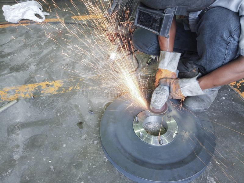 Worker grinding and cutting steel plate with a lot of spark royalty free stock photos