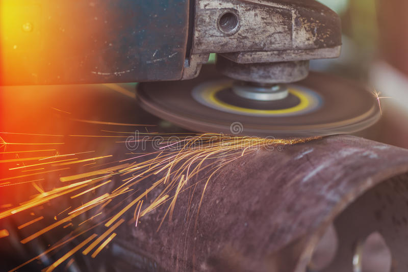 Worker grinding steel pipe with grinder royalty free stock image
