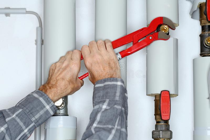 Worker with gripper in hand. Is fixing a pipe stock image
