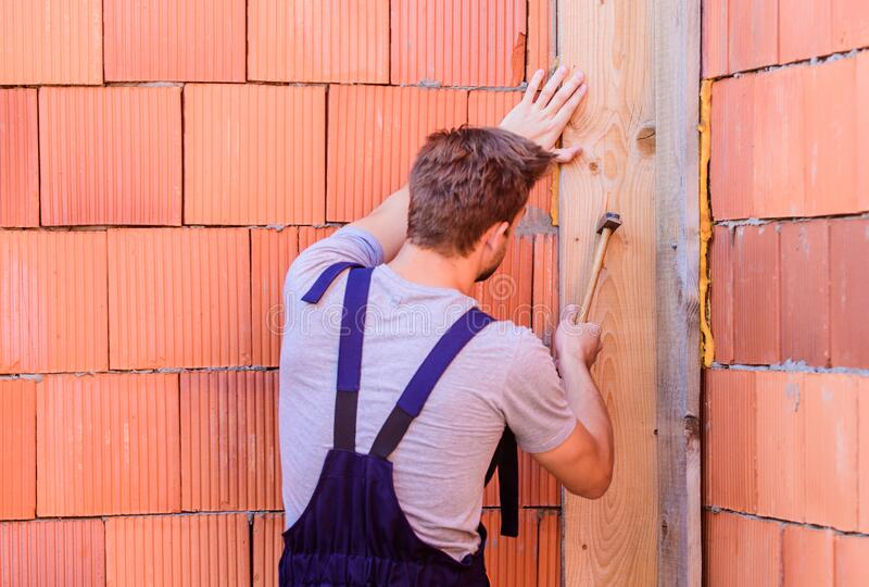 Worker with hammer brick wall background. Building and construction. Engineer with hammer tool. General maintenance and. Repair workers are hired for stock photo