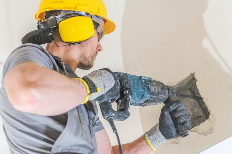 Worker with Hammer Drill. Drilling Holes in a Wall For a Wood Beam Installation. Construction Industry stock photography