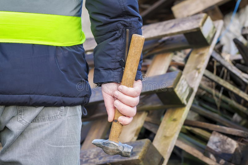 Worker with hammer near wooden pallets. In winter day royalty free stock photography