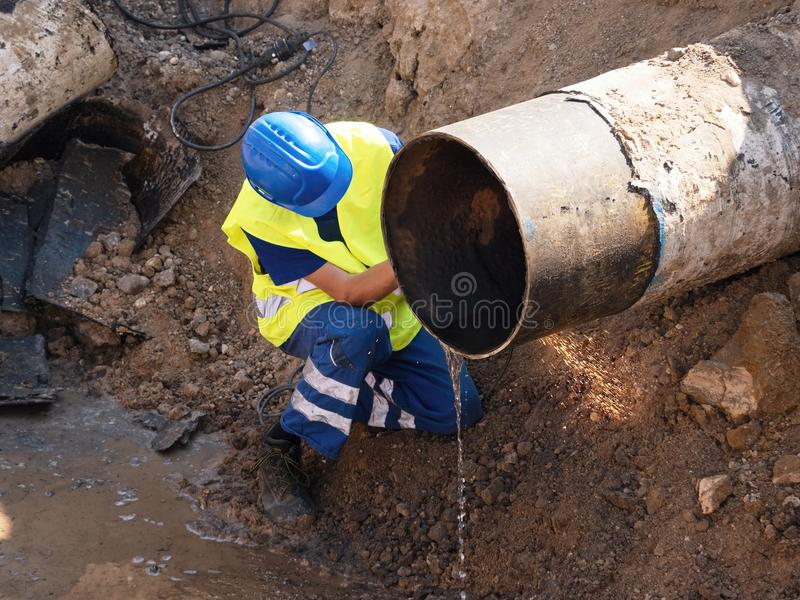Worker with hand grinder cut metal tube. Sparks are flying down to wet clay. Working staff in safety clot royalty free stock photos