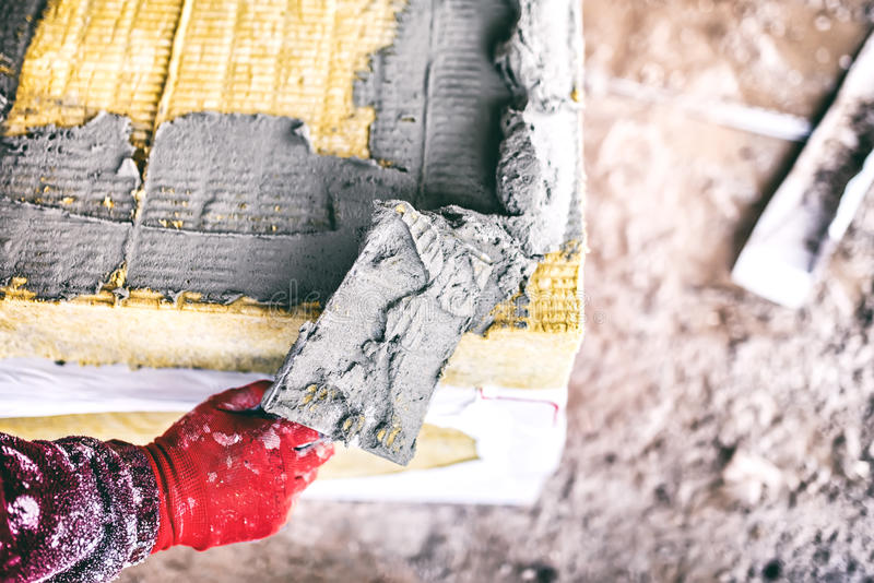 Worker hand on industrial construction site using a trowel and applying adhesive on thermal insulation panels stock images