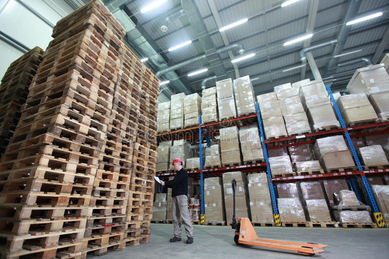 Download Worker With Hand Pallet Truck At Large  Stack Of Wooden Pallets In Storehouse Stock Photo - Image: 37701840