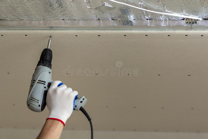 Worker hand with screwdriver connecting suspended drywall ceiling to metal frame. Renovation, construction and DIY concept. royalty free stock photo