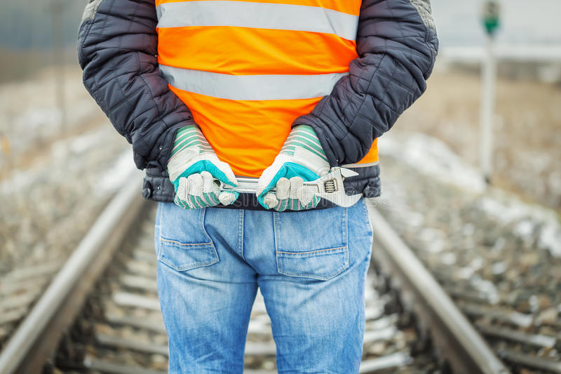 Worker hands with adjustable wrench on the railroad stock image