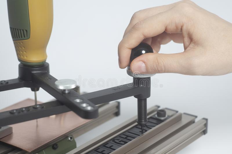 Worker hands on Engraving device pantograph with CNC engraver with letterpress alphabet. On a white background stock images