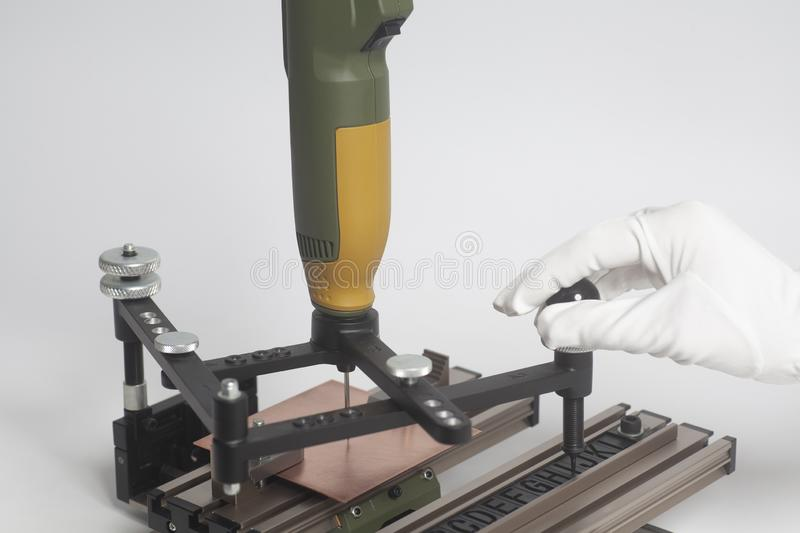 Worker hands on Engraving device pantograph with CNC engraver with letterpress alphabet. On a white background stock photo