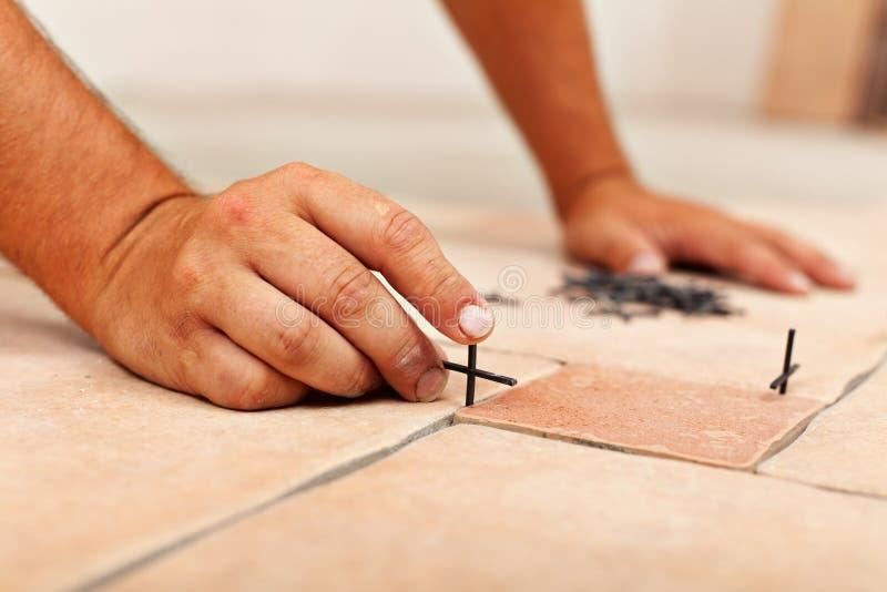 Worker hands placing spacers between ceramic floor tiles royalty free stock photos