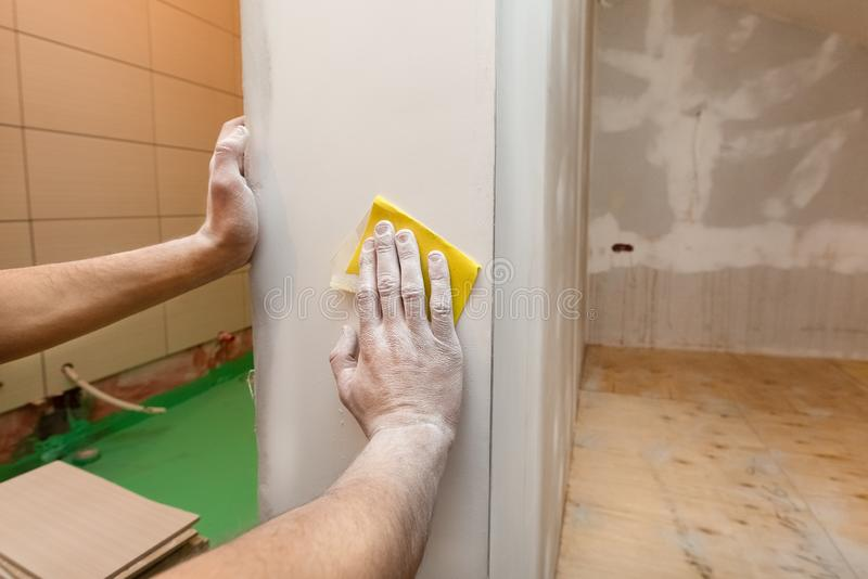 Worker hands is troweling by sandpaper the room wall in an apartment is inder construction, remodeling, renovation. Overhaul, extension, restoration and stock photo