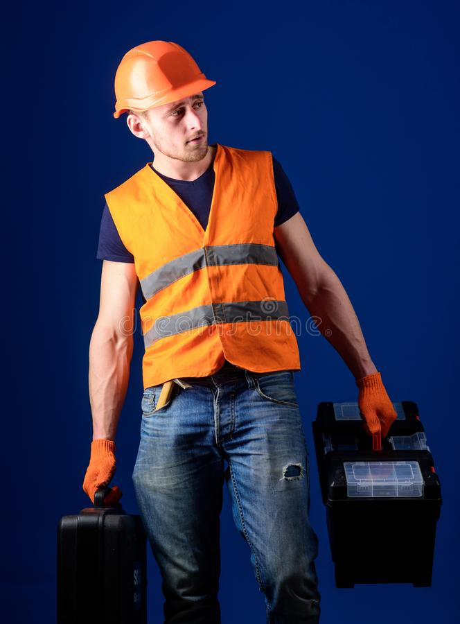 Worker, handyman, repairman, builder on calm face carries bags with professional tools. Man in helmet, hard hat holds. Toolbox and suitcase with tools, blue royalty free stock images