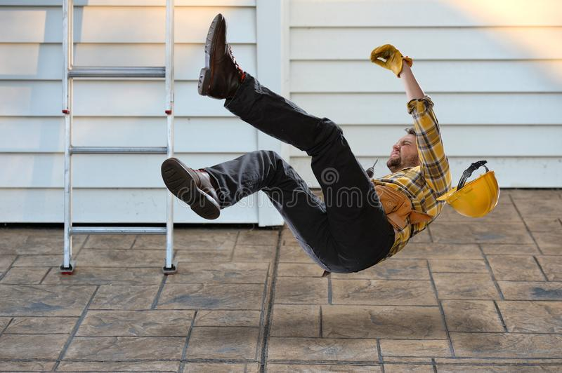 Worker Falling from Ladder. Worker with hard hat falling from ladder onto concrete floor stock photo