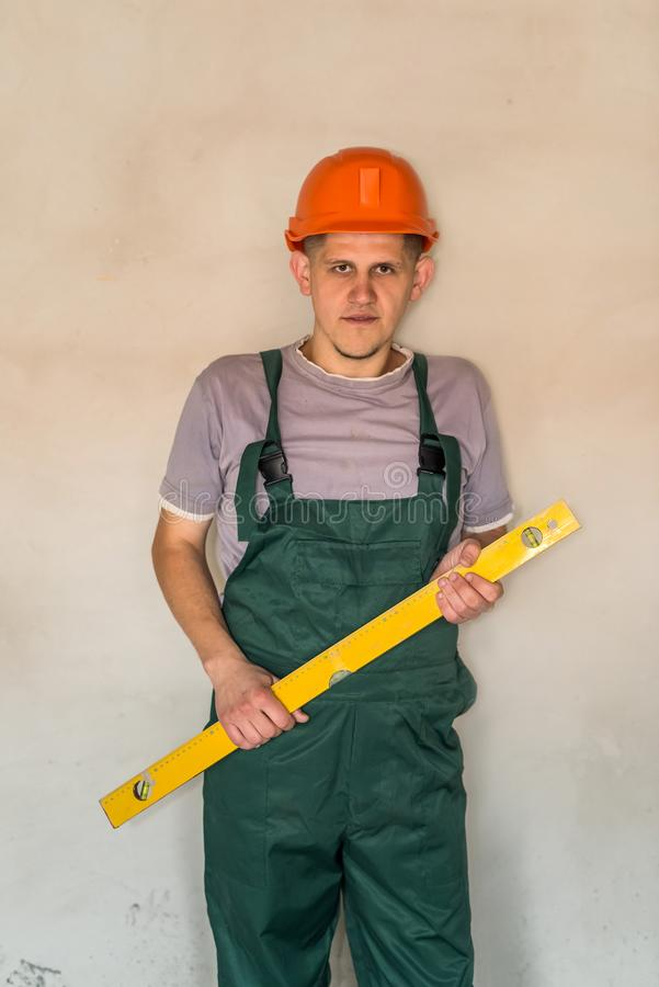Worker in helmet posing with water level tool royalty free stock photo