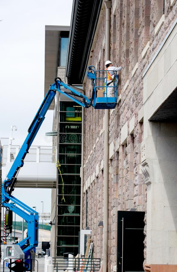Worker on a high lift. August 4. 2014 Denver Colorado USA; a worker on a high boom lift, does repairs on a brick building in down town Denver royalty free stock photos