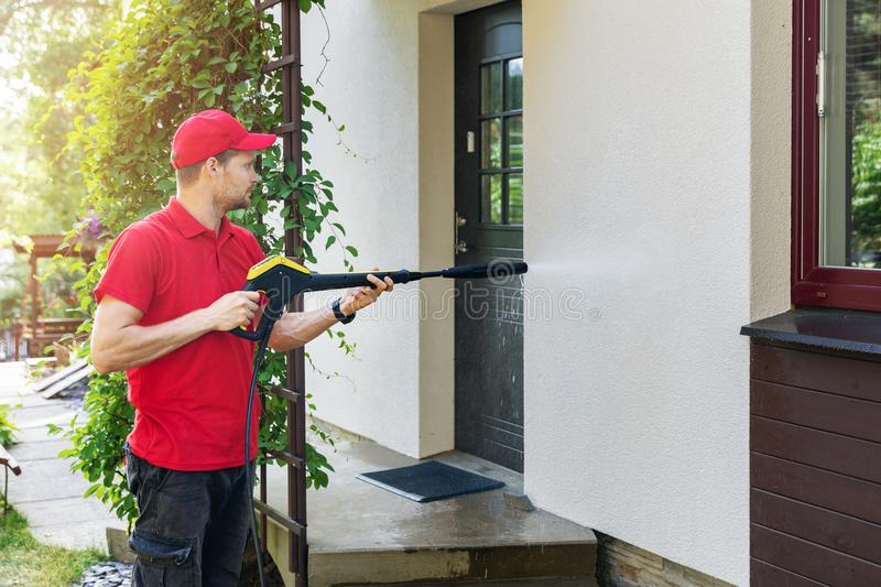 Worker with high pressure washer cleaning house facade. Worker in red uniform with high pressure washer cleaning house facade royalty free stock image