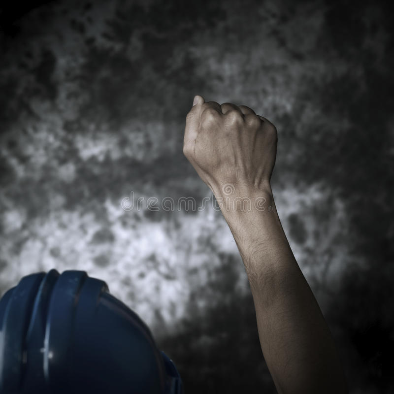 Worker with his fist raised to the air stock images