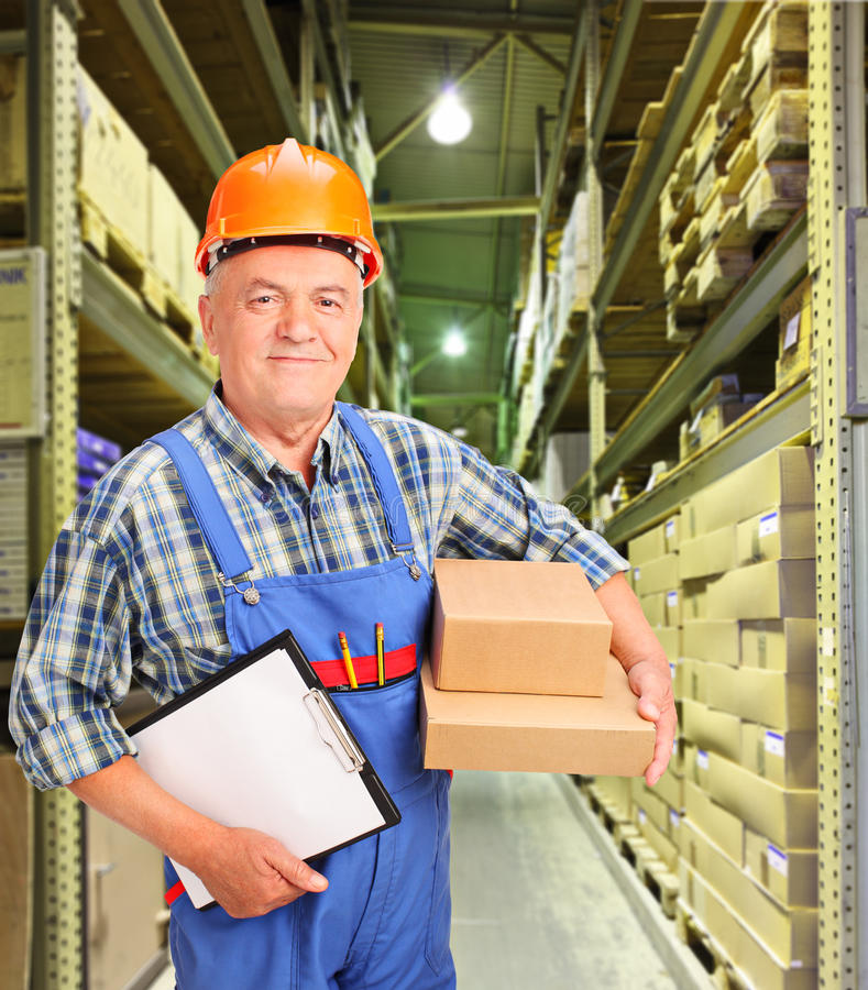 Worker holding boxes and clipboard at warehouse stock images
