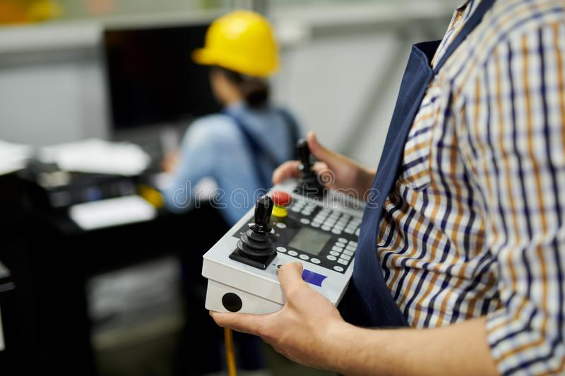 Worker Holding Machine Controller. Mid section shot of unrecognizable factory worker operating machine unit pressing buttons on control panel, copy space stock image