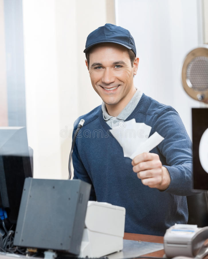 Worker Holding Tickets At Box Office Counter. Portrait of happy male worker holding tickets at box office counter stock image