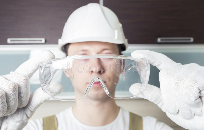 Worker holding transparent safety glasses royalty free stock photography