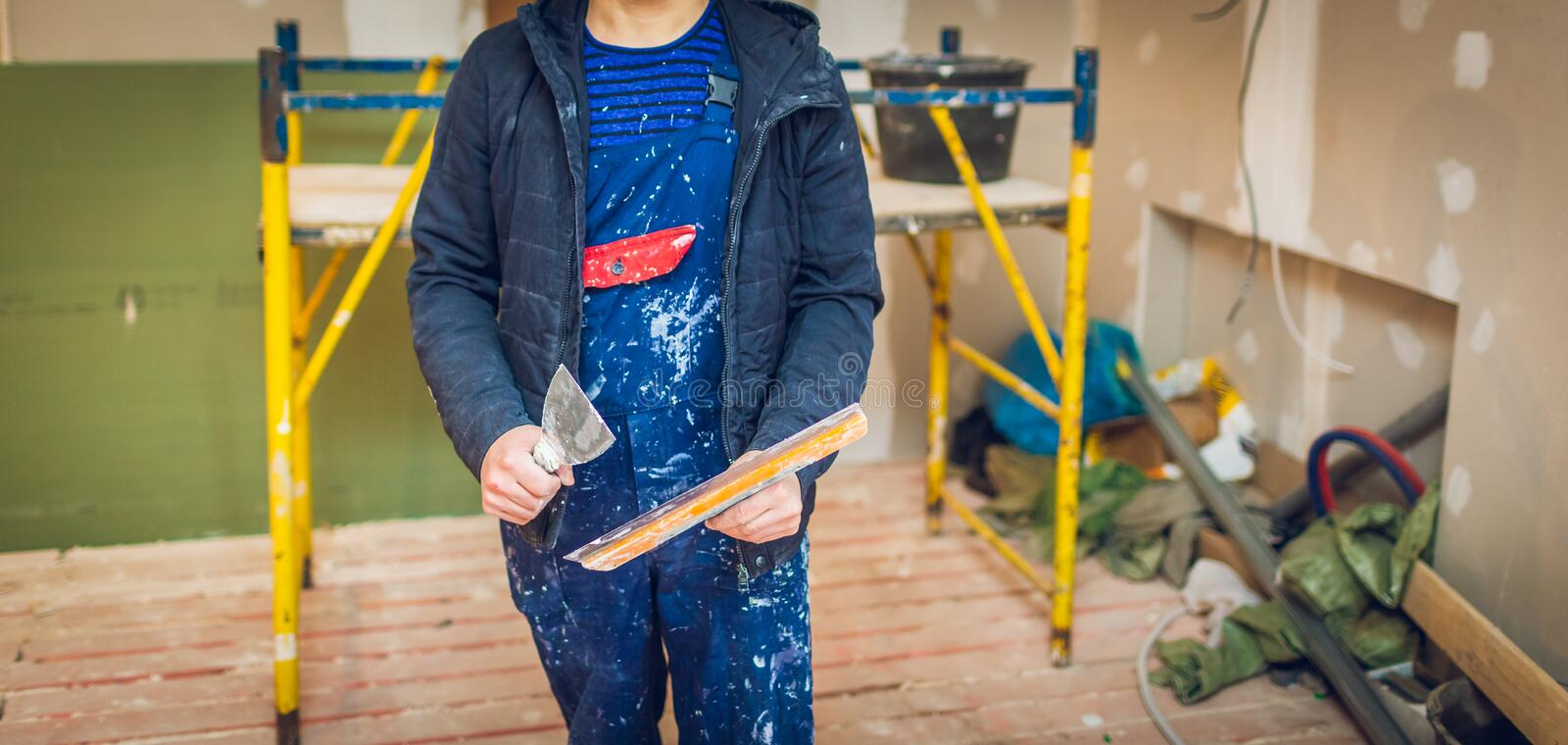 Worker holds a palette-knife for flattening the ceiling from wooden platform in room of apartment is inder construction. Remodeling, renovation, overhaul stock photography