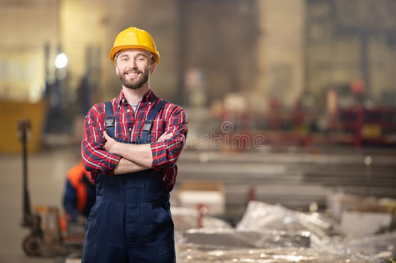 Worker of industrial plant. Young contemporary professional in machinebuilding industry standing inside workshop of large plant or factory stock image