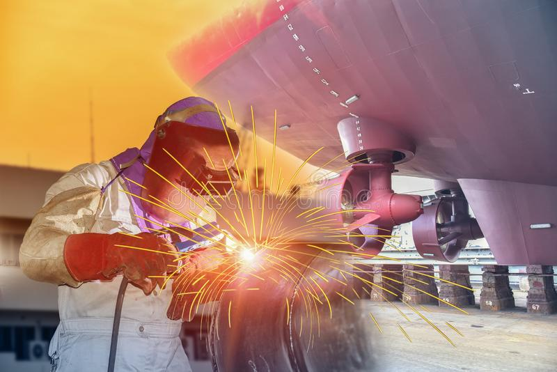 Shipyard worker welding ship repair. Worker Industrial with technician focus on welding process with equipment protective mask welder, leather gloves, PPE at royalty free stock image