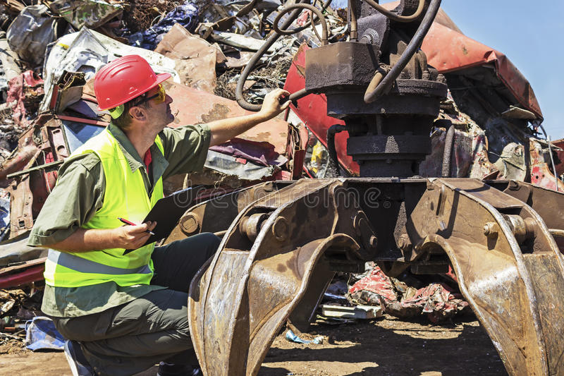Worker inspect crane on junkyard. Copy space available royalty free stock image